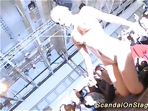 blonde buxom stunner drizzle on public stage